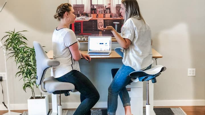 two girls talking while sitting on saddle chairs