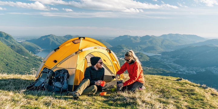 couple camping on mountain with yellow tent