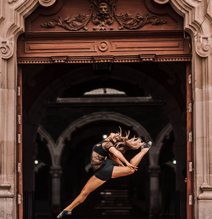 picture of a woman dancing in front a wooden gate
